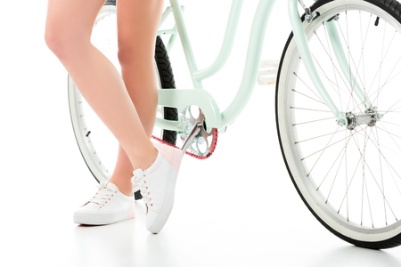 Close-up view of girl standing by cruiser bicycle isolated on white