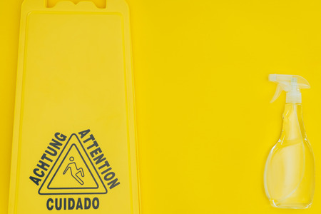 top view of wet floor sign and spray bottle isolated on yellow