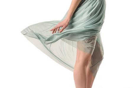 cropped view of elegant girl in transparent waving blue skirt, isolated on white Reklamní fotografie