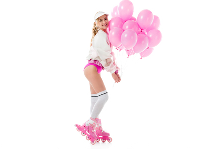 Blonde woman in pink clothes and roller blades holding balloons isolated on white