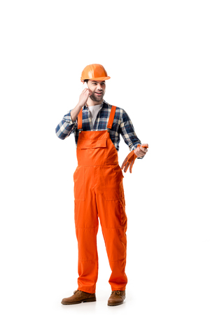 Young repairman in orange overall and hard hat talking on the phone isolated on white