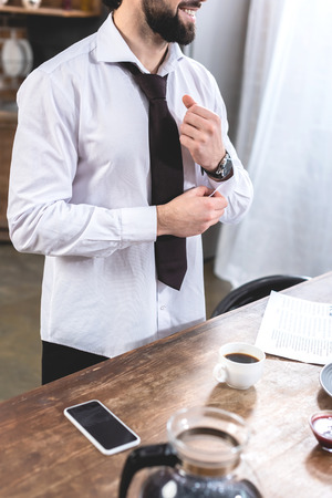 cropped image of loner businessman buttoning sleeve at kitchen
