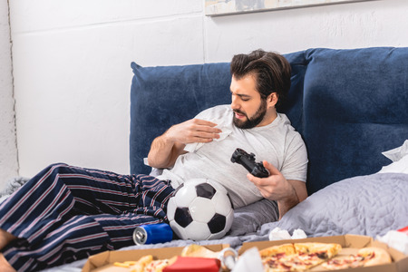 male loner playing video game in bedroom and removing spot on shirt Stock Photo