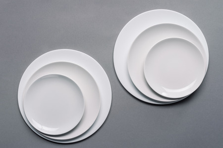 Shiny white kitchen ceramic plates on grey background