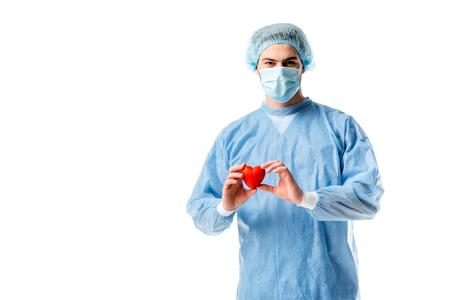 Cardiologo che indossa un'uniforme blu e tiene in mano un cuore giocattolo isolato su bianco Archivio Fotografico
