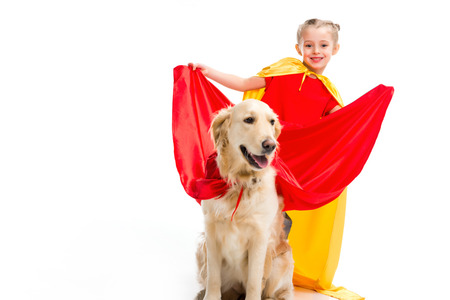Smiling supergirl expanding red cape on golden retriever isolated on white Stock Photo