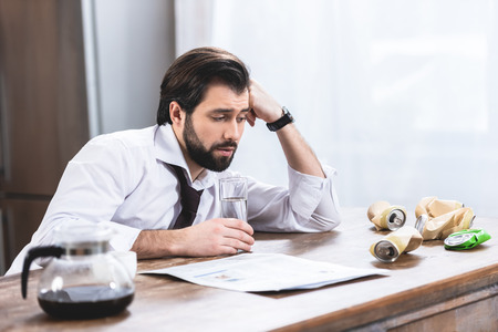 handsome loner businessman with hangover looking at crumpled cans on table at kitchen Stock Photo