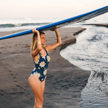 young sportswoman in swimming suit carrying blue surfing board on head on coastline