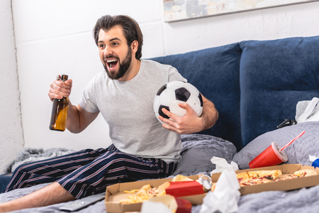 handsome loner watching football game with beer and screaming in bedroom Stock Photo