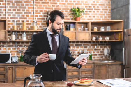 handsome loner businessman holding tablet and cup of coffee at kitchen Stock Photo