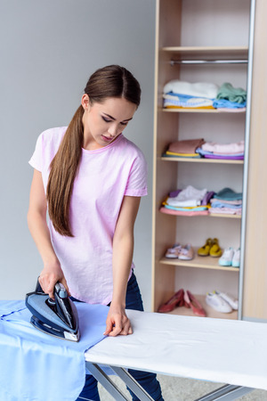 attractive young woman ironing clothing at home
