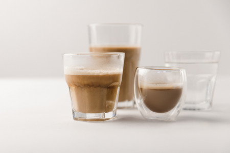 Glasses with coffee and milk on white background 스톡 콘텐츠