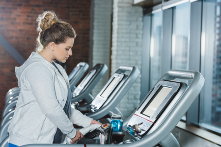 overweight woman adjusting treadmill before training