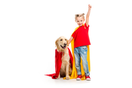 Dog standing in red cape with gesturing supergirl beside isolated on white