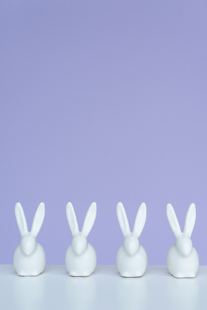 Bunny statuettes in row on violet background
