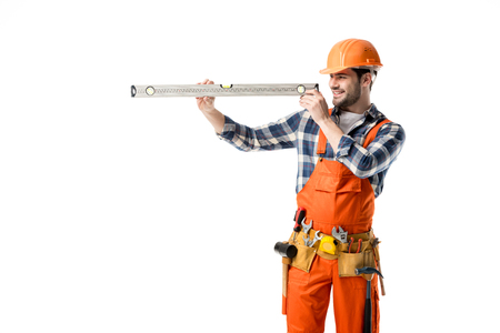 Young repairman in orange overall checking spirit level isolated on white