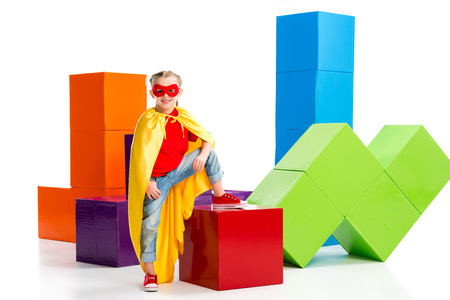 Supergirl in yellow cape and red mask for eyes standing on cube isolated on white