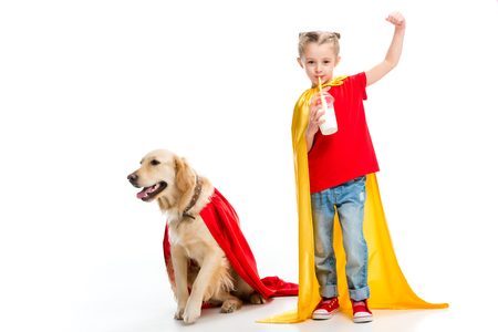 Supergirl drinking milkshake and gesturing with dog in red cape beside isolated on white Stock Photo