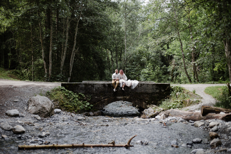 beautiful young wedding couple sitting on bridge above mountain river in Alps