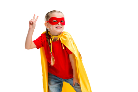 Smiling supergirl in yellow cape and red mask for eyes gesturing peace sign isolated on white Stock Photo