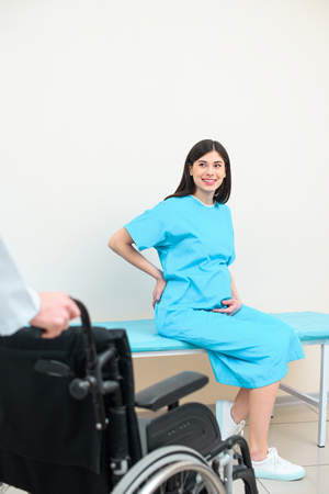 pregnant woman looking at obstetrician gynecologist with wheelchair