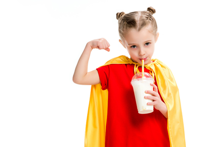 Little supergirl drinking milkshake and showing muscles isolated on white
