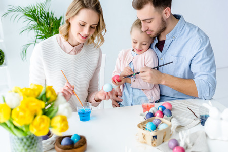 Daughter and parents painting Easter eggs Stock Photo