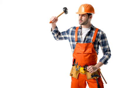 Bearded workman in orange overall and hardhat using hammer isolated on white