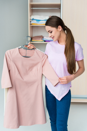 attractive young woman looking at dress on hanger