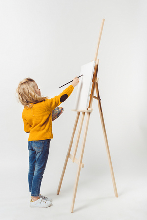 beautiful little child painting on canvas with oil paint on white