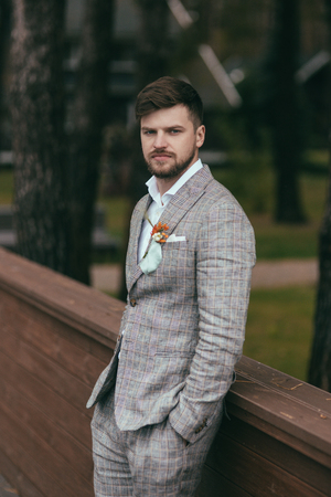 handsome bearded groom in trendy suit with buttonhole
