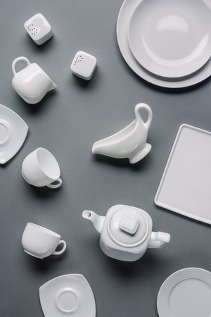 White tableware for dinner and tea time on grey background Stock fotó