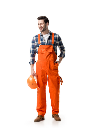 Young builder in orange overall holding hard hat isolated on white 写真素材