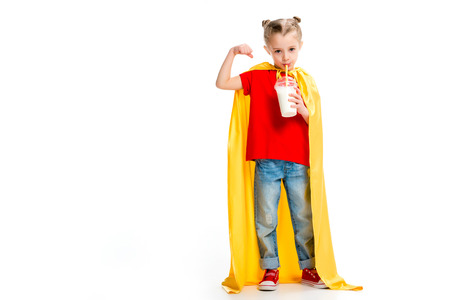 Supergirl in yellow cape drinking milkshake and showing muscles on hand isolated on white Stock Photo