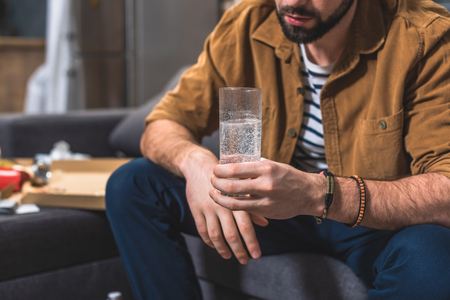 cropped image of loner with hangover holding glass of water at living room Stock Photo