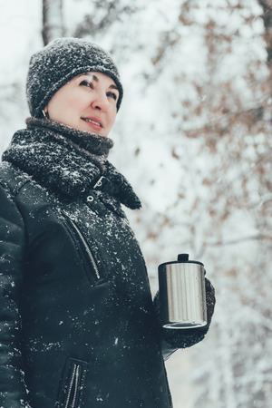 portrait of smiling woman with thermocup with hot drink looking away on street i winter Banco de Imagens