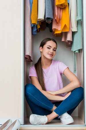 attractive young woman sitting inside of cabinet at home