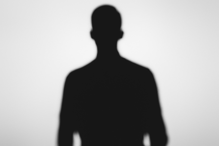 mysterious blurry shadow of spooky person standing on grey Reklamní fotografie