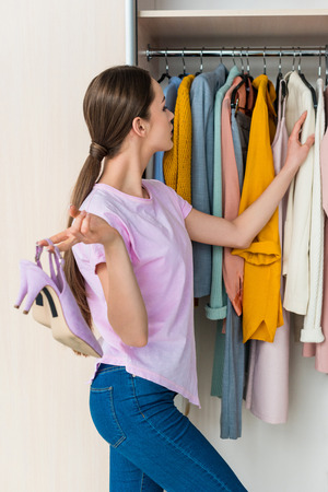 attractive young woman holding shoes and choosing clothes from cabinet at home