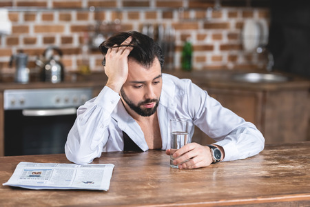 handsome loner businessman sitting at table in morning and looking at glass of water at kitchen