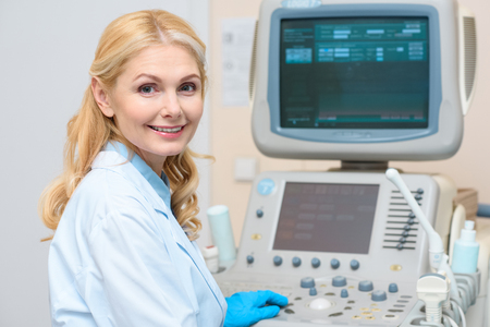 obstetrician gynecologist sitting at ultrasonic scanner and looking at camera Standard-Bild