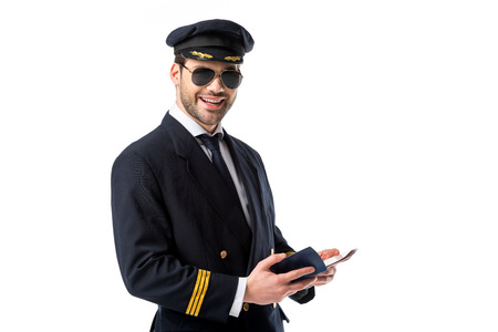 smiling pilot in uniform and sunglasses wit passport and ticket isolated on white