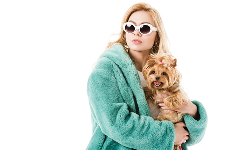 Blonde woman wearing fur coat holding cute dog isolated on white
