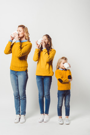 mother and daughters drinking coffee together on white