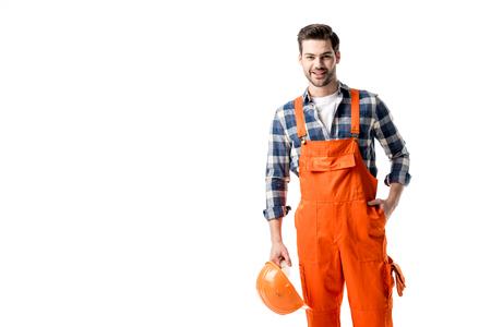 Lächelnder Handwerker im orangefarbenen Overall mit Schutzhelm isoliert auf weiß Standard-Bild