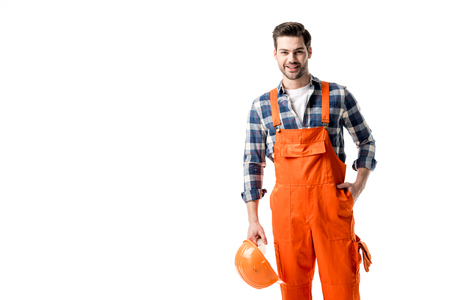 Smiling handyman in orange overall holding hard hat isolated on white