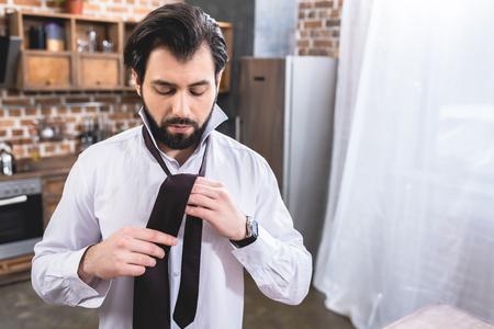 handsome loner businessman tying necktie at home Stock Photo