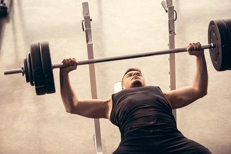 Guapo deportista levantando pesas en press de banca en el gimnasio