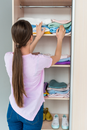 attractive young woman choosing clothes from stack Stock Photo