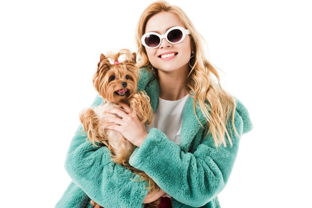Attractive young woman dressed in mint fur coat holding Yorkshire terrier isolated on white Stock Photo